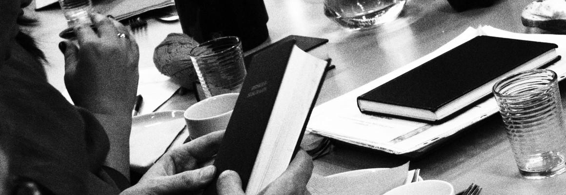 Hånd med salmebog på mødebord